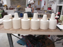 6 cups sitting atop they molds ready to has slip poured inside and multiplicated.