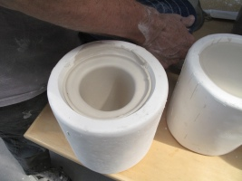 2 cup molds, 1 has been filled with slip, left to sit, then poured out, leaving the clay shell vessel. The other mold still este filled with slip.
